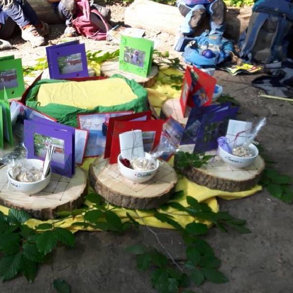 Selbstgebastelte Abschiedsgeschenke (Das Spiel Mühle, eine Schüssel mit dem Vornamen des Kindes, eine Karte und Müsli) für die Vorschulkinder sind im Kreis angeordnet.